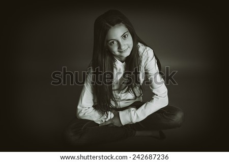 Beautiful little girl sitting with her legs crossed. Gray background. Sepia picture. - stock photo