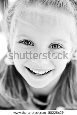Beautiful little girl smiling. Black and white - stock photo