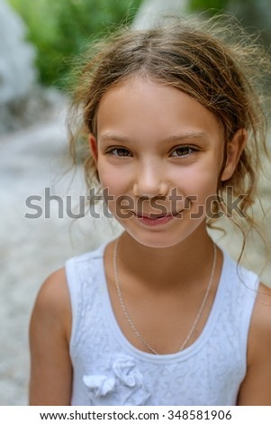 Beautiful little girl smiling on background of summer green park.