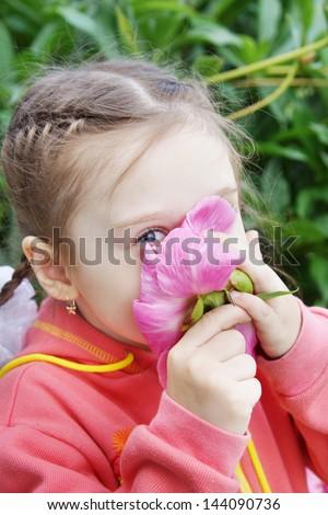 Beautiful Little Girl Sniffs a Flower - stock photo
