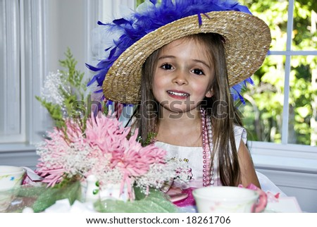 Beautiful little girl wearing a party hat and beads with a pretty smile. - stock photo
