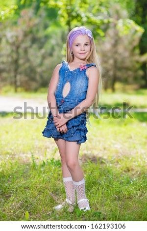 Beautiful little girl wearing jeans dress posing outdoors - stock photo