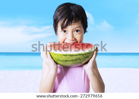 Beautiful little girl wearing swimsuit on the beach while eating a fresh watermelon - stock photo