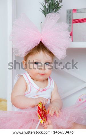 beautiful little girl with a big bow on her head with a lollipop in hand - stock photo