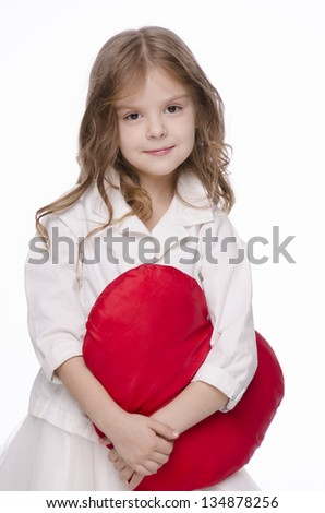 beautiful little girl with a big toy red heart on a white background, closeup - stock photo