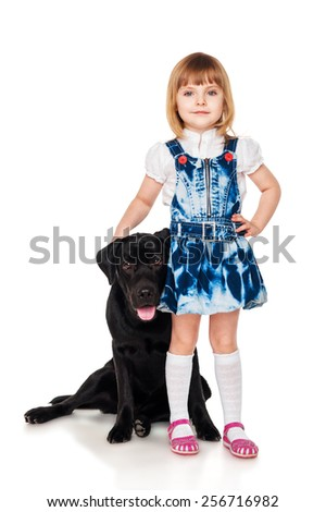 Beautiful little girl with a black Labrador - stock photo
