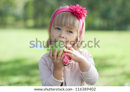 Beautiful little girl with a flower in her hair eating an apple.