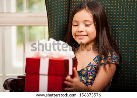 Beautiful little girl with a present she just received for her birthday - stock photo