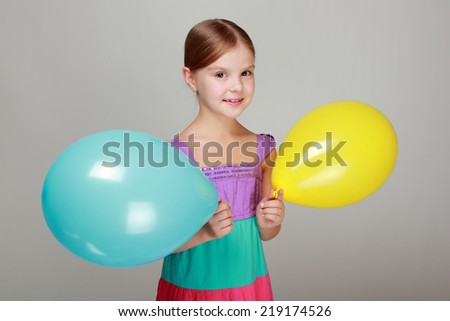 Beautiful little girl with a sweet smile, holding a yellow and blue air balloon on Holiday - stock photo