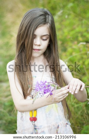 Beautiful little Girl  with a wild  flower - stock photo