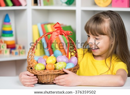 Beautiful little girl with basket of Easter eggs - stock photo