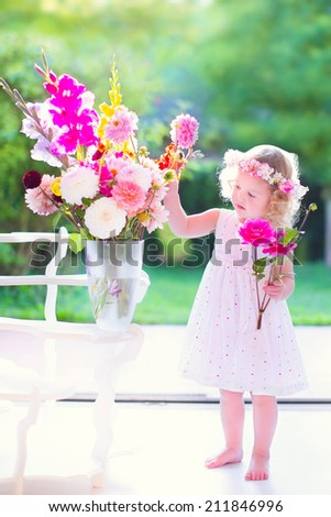 Beautiful little girl with curly hair wearing a white dress smelling flowers, colorful bouquet in a big vase standing next to a big window and door to the garden on a sunny summer day at home - stock photo