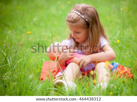 beautiful little girl with doll on the nature