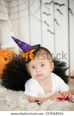 beautiful little girl with Down syndrome in a suit a little witch - stock photo