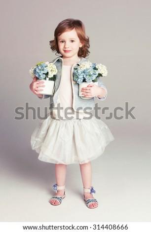 Beautiful little girl with flowers. Studio shot  - stock photo