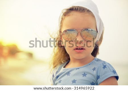 Beautiful little girl with glasses and headscarf on beach.