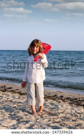 beautiful little girl with guitar on beach