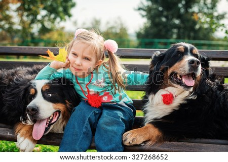 Beautiful little girl with her dogs, autumn. Bernese Mountain Dog