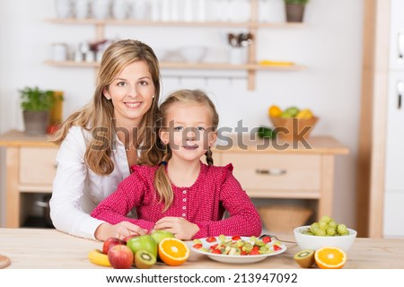Beautiful little girl with her mother in the kitchen preparing a fresh fruit salad as the two pose side by side looking at the camera with charming friendly smiles - stock photo