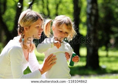 beautiful little girl with her mother on nature