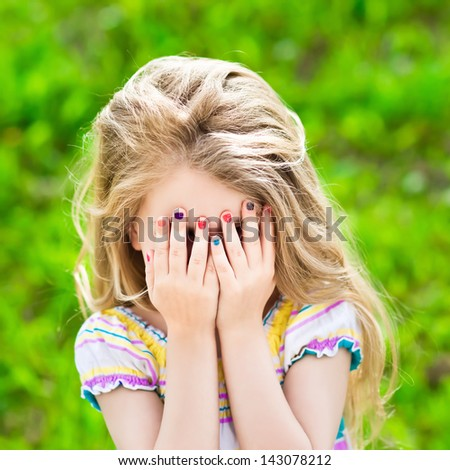 Beautiful little girl with long blond hair and many-coloured manicure covering her eyes with her hands - stock photo