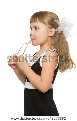 Beautiful little girl with long, blonde, lush hair, which is braided large white bows, in black short dress. The girl holds glasses . Closeup - Isolated on white background - stock photo