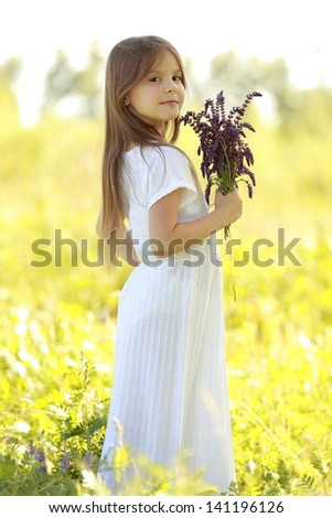 Beautiful little girl with long hair in a white dress holding flowers of the field on the background of the park in the summer sunshine - stock photo