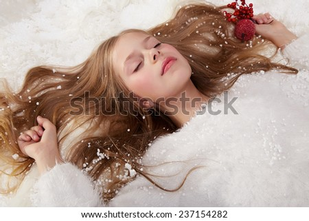 Beautiful little girl with long hair in a white winter sweater lying in the snow under the Christmas tree gift for New Year Merry Christmas card - stock photo