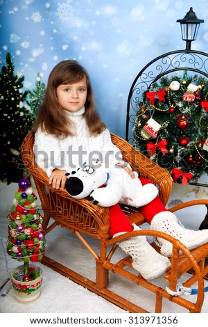 beautiful little girl with long vollosami in knit sweater sitting in wicker sleigh holding a teddy bear on the background of Christmas decorations - stock photo