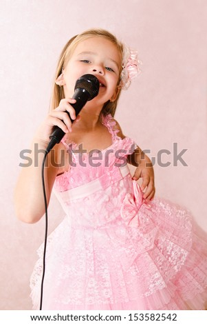 Beautiful little girl with microphone in princess dress isolated  - stock photo