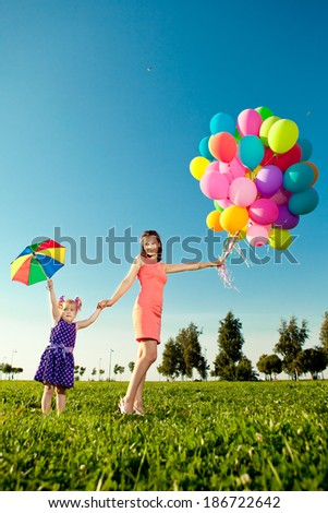 Beautiful little girl with mother colored balloons and rainbow umbrella holding  in  the park. Smiling child and mom on a field with flowers. Kid with mum rest on the  nature. Family outdoor - stock photo