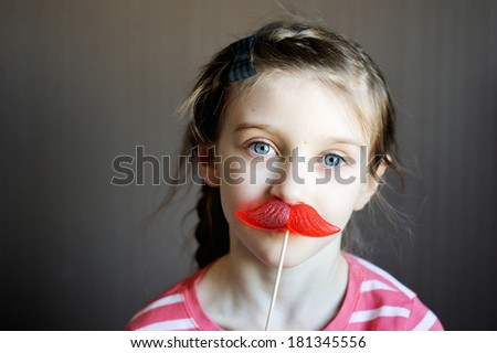 Beautiful little girl with mustache-shaped lollipop - stock photo