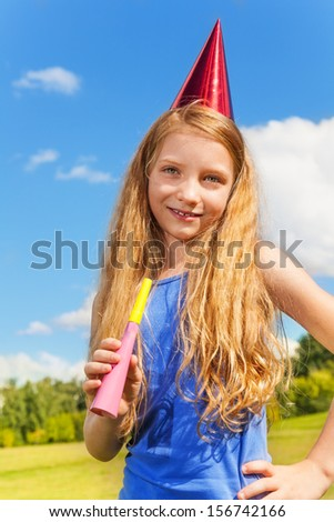 Beautiful little girl with noisemaker horn and birthday party cap standing outside with happy expression on sunny summer day - stock photo