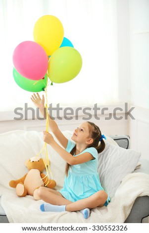 Beautiful little girl with teddy bear and colorful balloons sitting on sofa, on home interior background - stock photo