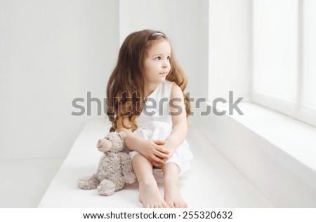 Beautiful little girl with teddy bear in white room near window - stock photo