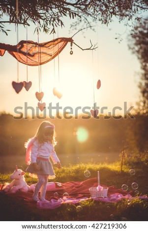 beautiful little girl with wings outdoors - stock photo