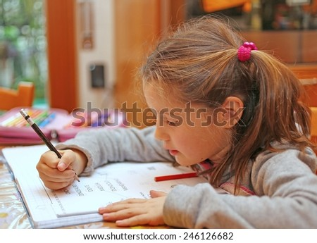 beautiful little girl writes the homework on notebook - stock photo