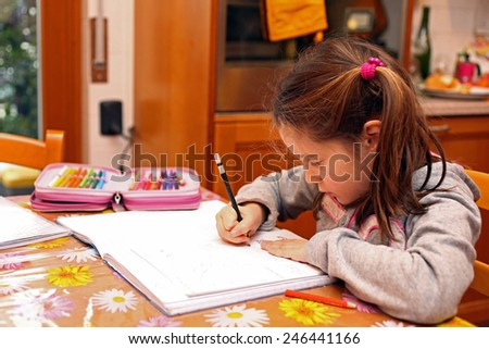 beautiful little girl writes with pencil on notebook exercises - stock photo