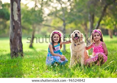 Beautiful little girls and golden retriever outdoors - stock photo