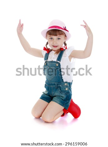 Beautiful little hairy girl with short bangs and braids in which the braided bows on his knees in the hat, denim overalls and red boots - isolated on white background - stock photo
