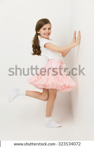 Beautiful little happy girl in tutu skirt standing near white wall - stock photo