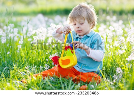 Beautiful little kid boy having fun with traditional Easter egg hunt on warm sunny day, outdoors. Celebrating Easter holiday.