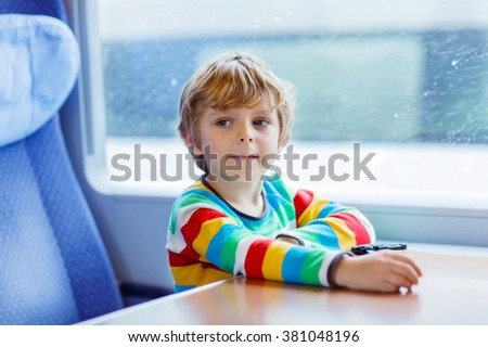 Beautiful little kid boy looking out train window outside, while it moving. with rain outside. Child going on vacations and traveling by railway.