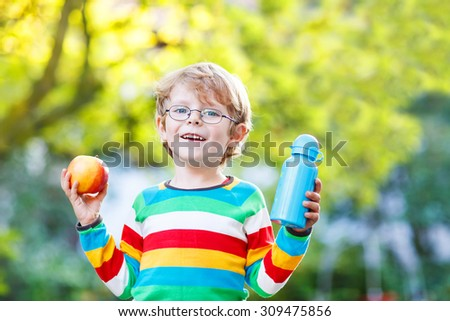 Beautiful little kid boy with  apple and drink bottle on his first day to elementary school or nursery. Outdoors.  Back to school, kids, lifestyle concept - stock photo