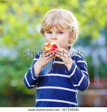 Beautiful little kid boy with apple on his first day to elementary school or nursery. Outdoors.  Back to school, kids, lifestyle concept. Child eating healthy food - stock photo