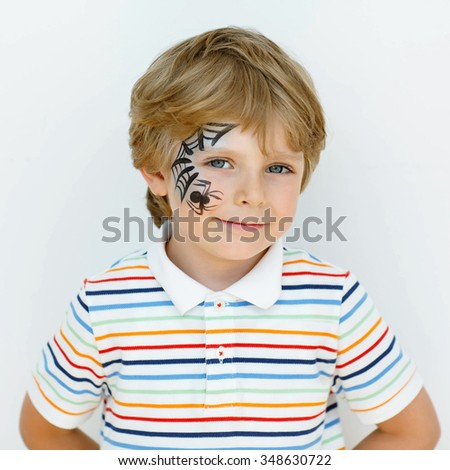 Beautiful little kid boy with face painted with a spider web, on a birthday party. happy child having fun. - stock photo
