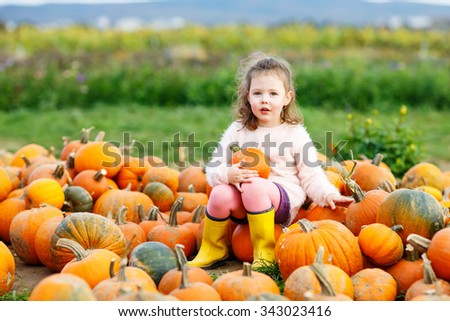 Beautiful little kid girl having fun with farming on organic pumpkin patch. Traditional family festival with children, thanksgiving and halloween concept. Cute farmer.