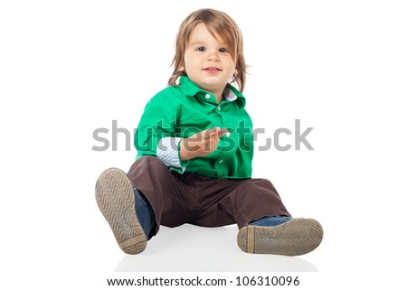 Beautiful little kid, 2 years old boy, sitting on the floor and looking at camera, wearing shirt and jeans. High resolution image isolated on white background with copy space. Studio shot. - stock photo