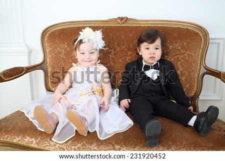 Beautiful little kids in costumes bride and groom sitting on couch - stock photo