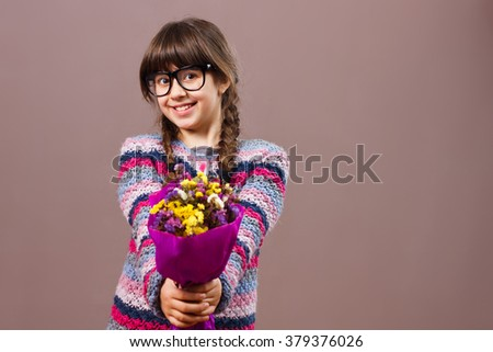 Beautiful little nerdy girl is holding bouquet of flowers.Flowers for you! - stock photo